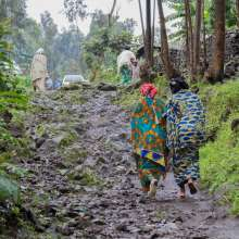 Sifa and Nyria, two women living in a project in the democratic republic of Congo, walk down a rough road