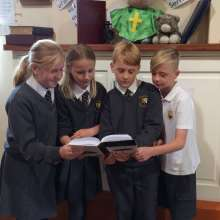 School children reading bible for Bible in a day campaign