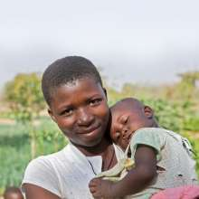 Colette, the focus of Christian Aid's Christmas Appeal, holds a baby