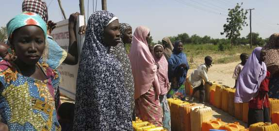 Girls in a camp in Borno state, Nigeria stand with water pots