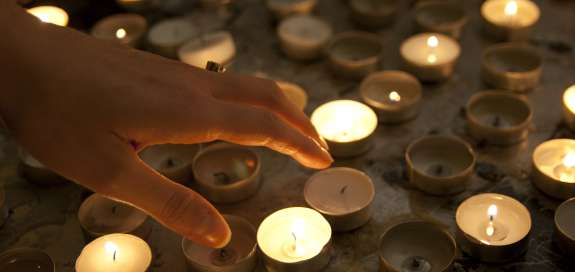 Hand reaching towards reflective candles