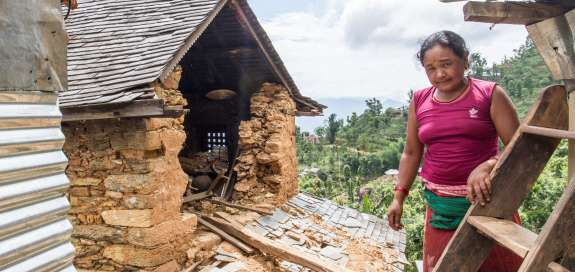 A woman stands outside her house which has partly collapsed from the earthquake in Nepal