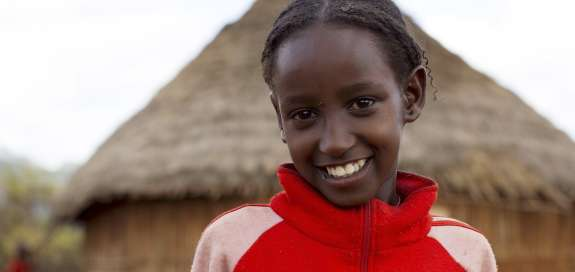 Ten-year-old Negele Dhiba stands in front of a house in her village in Ethiopia