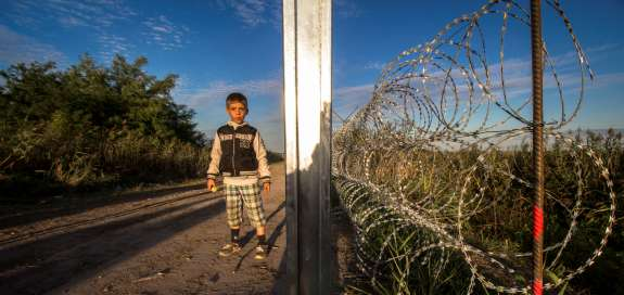 Young boy walking along road next to large coils of barbed wire