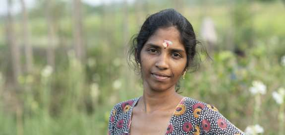 Kasthuri's stands in front of green crops
