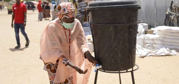 Christian Aid staff member Bintu washes her hands in a camp for displaced people in Nigeria