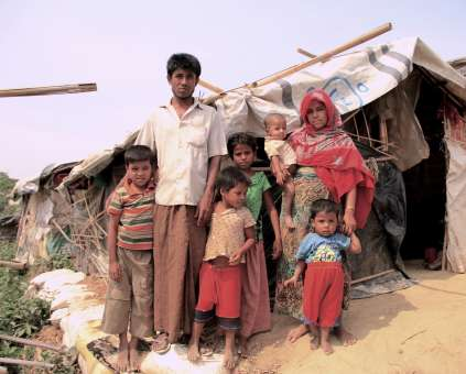Rohingya resident Mohammad Ilias and his family outside their wind and rain-damaged shelter in Jamtoli's H Block. Strong winds blew off Ilias's tarpaulin roof and cracked the flimsy bamboo lattice-work that forms the shelter's walls.