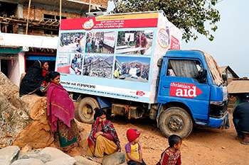 A group of Nepalese children next to a Christian Aid van