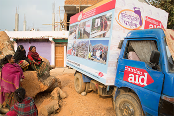 Nepalese women stand next to a Christian Aid truck