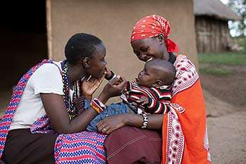 Narok County, Kenya: Christine Parakuo, left, and plays with her son Kishoyian Samson held by Elizabeth Ntunkosio.