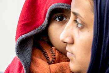 Photo from our refugee appeal: profile view of a woman in front of a child wearing a hood
