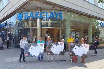 Campaigners holding Prudence the Pig petitions outside a Barclays bank.