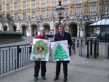 Anna Jane Evans and David Jones holding placards outside the Houses of Parliament.
