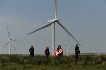 Four people standing in front of a wind turbine