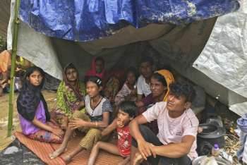Rohingya crisis 2017 - a family sit on the floor under a makeshift shelter