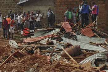 People standing by homes ruined by mudslide in Sierra Leone