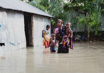 Woman and children standing in flood water.