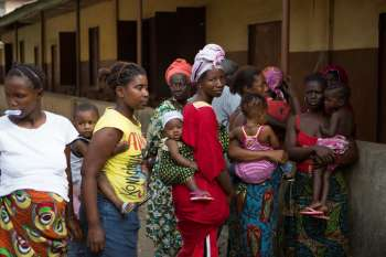 Women with children queue at health clinic