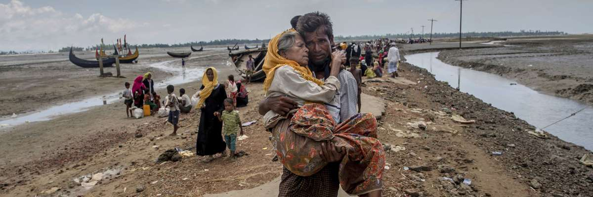 A barefoot man carries his frail-looking mother after crossing the border into Bangladesh.