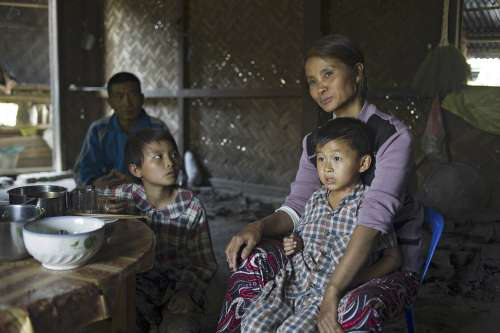 Asar Mi, from Myanmar, sits with two of her children