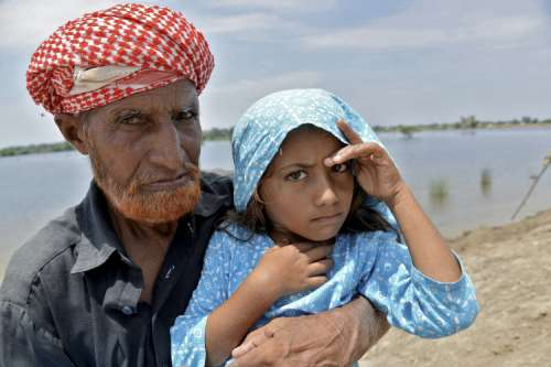 Elderly man with young girl with water behind them