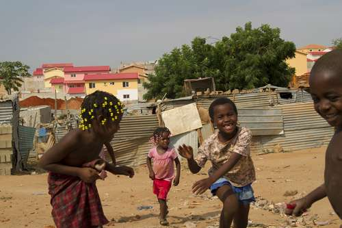 Children play in front of tin shacks in Angola, built from the remains of homes that have been bulldozed repeatedly by the government in Cambamba I, a neighbourhood in Luanda, Angola's capital. The homes are being cleared to make way for new houses for Angola's elite, which can be seen being built in the background. More than 4 million people are estimated to have been displaced during Angola's 27-year civil war.