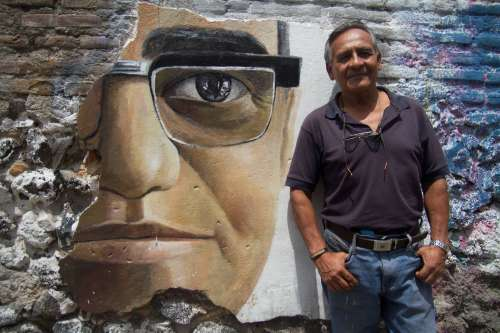 El Salvador poetry teacher stands next to Oscar Romero mural