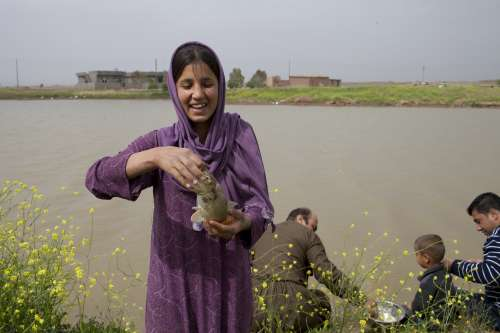 April 2013, Zanan Bchuk, near Chomchomal, northern Iraq Rojan Wahid, 15, takes a fish caught by her uncle Mllko (centre, back) so her mother can prepare it for lunch.  Zanan Bchuk's peaceful atmosphere belies its turbulent history. In 1988 it was largely destroyed by bombs during the Ba'ath regime's Anfal campaign. When the community returned, the destruction was so complete that they struggled to identify individual homes.