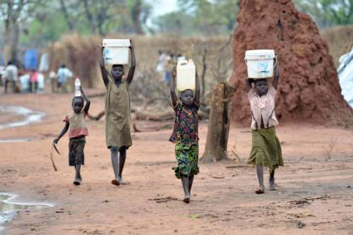 children carrying water in South Sudanese refugee camp