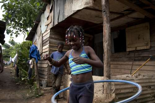 Carolina de Jesus plays with her hula hoop. Her brother Joel explained how he knows they need to run away if they have a red alert.