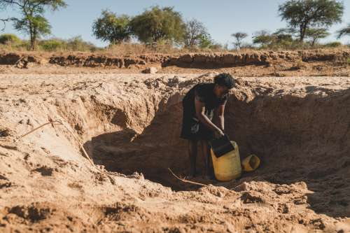 Faith collects water from a nearly dry dam in Makueni county, Kenya