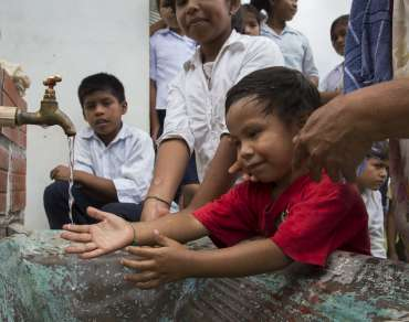 Children in Bolivia holding their hands under a running water tap - Christian Aid Gifts in Wills