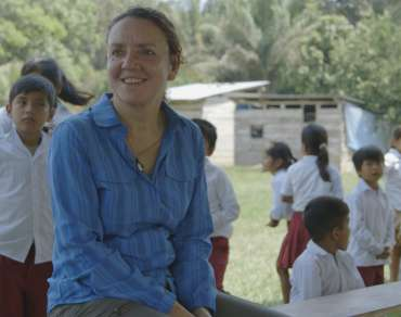 Eleri Davies is sitting with children at a school in Bolivia