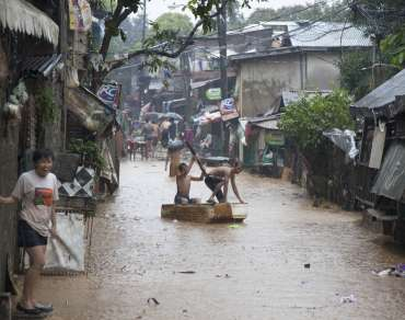 Banaba, San Mateo in Manila is flooded with local residents standing outside makeshift houses in the rain