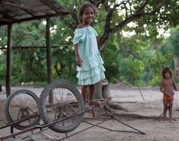 A young malnourished girl, Marcia Moreno, stands on old, upside down cart and a young child stands behind her