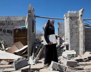 A woman holding a sketch pad walks over the remains of a building that has been destroyed in Gaza in 2014