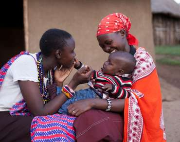 A woman sits with her son on her knee whilst another woman smiles at him in Narok County, Kenya