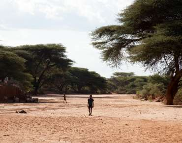 A boy walks along a dried out riverbed in Ethiopia