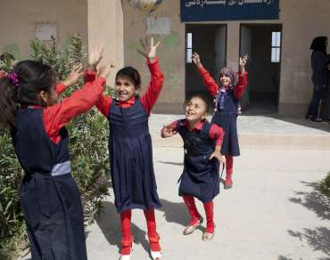 4 school girls play outside their school in Northern Iraq