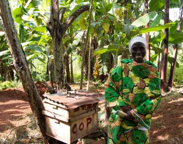A female coffee farmer standing in front of trees in Burundi