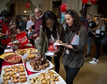 Two young women choosing cakes at a Christian Aid bake sale fundraiser