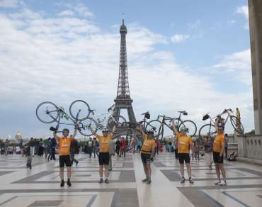 Christian Aid cyclists holding their bikes above their heads in front of the Eiffel Tower in Paris