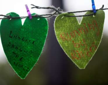 A string of green, felt hearts with prayers written on them