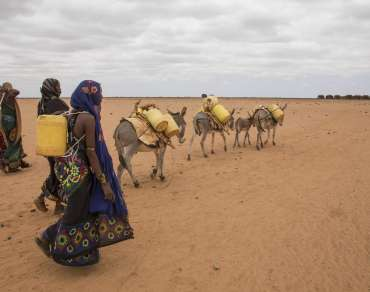 Group of women walk across arid desert