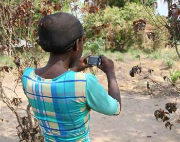 Pauline Ola, community health volunteer in Nigeria, using her camera provided as part of the Picture Power project