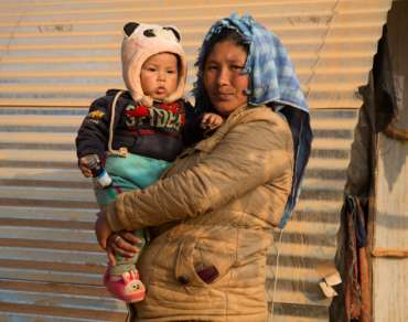Displaced woman holding small child, Nepal