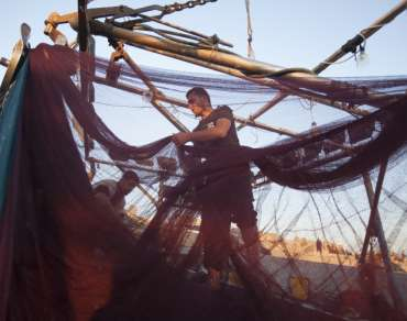 Fishermen resetting nets in Gaza City