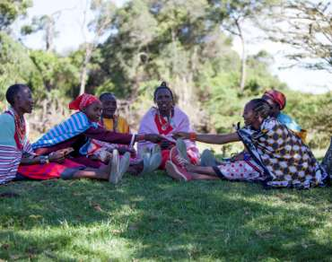 Maternal health mothers' support group, sat outside on grass, western Kenya