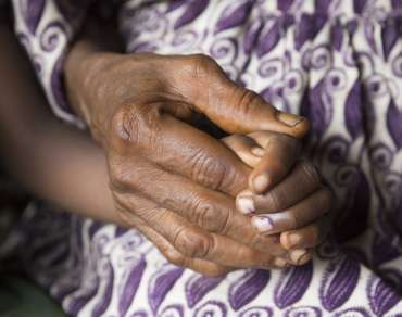 6-year-old Hawa holds her grandmother's hand - Sawula, Sierra Leone