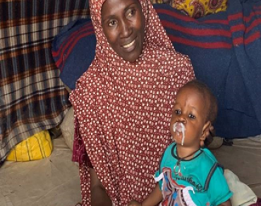 Aisha giving Bashir with supplementary feeding after discharge from Stabilization Centre